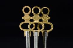 Τρία παλαιά κλειδιά ρολογιών τσεπών ορείχαλκου που στέκονται στο σκοτάδι Στοκ Εικόνες