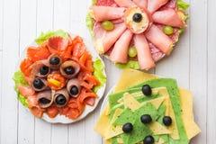 Τρία πιάτα των ορεκτικών Ρόλος ζαμπόν με το τυρί και κόκκινα ψάρια, τεμαχίζοντας διαφορετικοί τύποι τυριών στοκ φωτογραφία με δικαίωμα ελεύθερης χρήσης