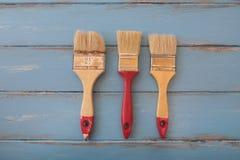 Τρία πινέλα πέρα από τους μπλε χρωματισμένους ξύλινους πίνακες Στοκ φωτογραφία με δικαίωμα ελεύθερης χρήσης