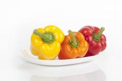 Τρία πιπέρια σε ένα πιάτο Στοκ Εικόνες