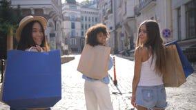 Τρία πολυφυλετικά κορίτσια με το χαμόγελο τσαντών αγορών απόθεμα βίντεο