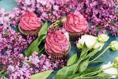 Τρία πορφυρά cupcakes με τα άσπρα τριαντάφυλλα και πασχαλιά στον μπλε πίνακα Στοκ Εικόνα