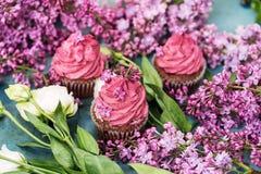 Τρία πορφυρά cupcakes με τα τριαντάφυλλα και πασχαλιά στον μπλε πίνακα Στοκ εικόνες με δικαίωμα ελεύθερης χρήσης