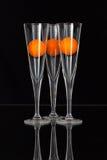 Τρία ποτήρια της σαμπάνιας και των πορτοκαλιών σφαιρών γκολφ Στοκ Εικόνες