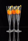 Τρία ποτήρια της σαμπάνιας και των πορτοκαλιών σφαιρών γκολφ Στοκ εικόνες με δικαίωμα ελεύθερης χρήσης