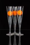 Τρία ποτήρια της σαμπάνιας με τις πορτοκαλιές σφαίρες γκολφ Στοκ εικόνες με δικαίωμα ελεύθερης χρήσης