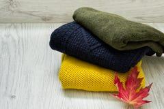 Τρία πουλόβερ και ένα φύλλο σφενδάμου σε ένα ξύλινο υπόβαθρο μοντέρνη έννοια Στοκ Εικόνες