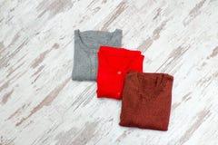 Τρία πουλόβερ σε ένα ξύλινο υπόβαθρο μοντέρνη έννοια Στοκ Φωτογραφία