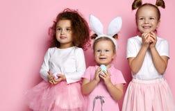 Τρία που ντύνονται επάνω για τα κορίτσια παιδιών διακοπών με τα χρωματισμένα αυγά περιμένουν ένα θαύμα την ημέρα Πάσχας στοκ φωτογραφίες