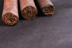 Τρία πούρα στην ανασκόπηση δέρματος Στοκ φωτογραφία με δικαίωμα ελεύθερης χρήσης