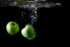 Τρία πράσινα μήλα που καταβρέχουν στο νερό στο μαύρο υπόβαθρο διάστημα αντιγράφων Στοκ Εικόνες