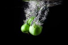 Τρία πράσινα μήλα που καταβρέχουν στο νερό στο μαύρο υπόβαθρο διάστημα αντιγράφων Στοκ εικόνα με δικαίωμα ελεύθερης χρήσης