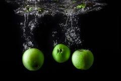 Τρία πράσινα μήλα που καταβρέχουν στο νερό στο μαύρο υπόβαθρο διάστημα αντιγράφων Στοκ φωτογραφία με δικαίωμα ελεύθερης χρήσης