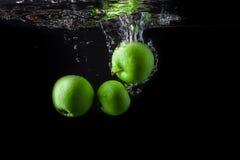 Τρία πράσινα μήλα που καταβρέχουν στο νερό στο μαύρο υπόβαθρο διάστημα αντιγράφων Στοκ εικόνες με δικαίωμα ελεύθερης χρήσης