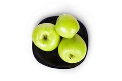 Τρία πράσινα μήλα σε ένα μαύρο πιάτο Στοκ φωτογραφίες με δικαίωμα ελεύθερης χρήσης