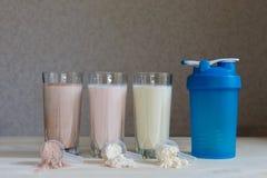 Τρία πρωτεϊνικά κουνήματα ορρού γάλακτος γάλακτος στα φλυτζάνια γυαλιού τακτοποιούνται σε μια σειρά με τρεις σέσουλες της πρωτεΐν στοκ εικόνες με δικαίωμα ελεύθερης χρήσης