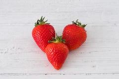 Τρία στις υγιείς σκωτσέζικες φράουλες μιας καρδιών μορφής σε έναν λευκό πίνακα σανίδων στοκ φωτογραφίες