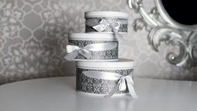 Τρία στρογγυλά κιβώτια δώρων εορτασμού με τα ασημένια τόξα κορδελλών στον άσπρο πίνακα Ο σωρός παρουσιάζει στο εσωτερικό πολυτέλε Στοκ Εικόνα