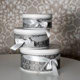 Τρία στρογγυλά κιβώτια δώρων εορτασμού με τα ασημένια τόξα κορδελλών στον άσπρο πίνακα Ο σωρός παρουσιάζει στο εσωτερικό πολυτέλε Στοκ Φωτογραφίες