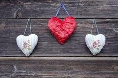 Τρία σύμβολα καρδιών υφασμάτων στον παλαιό ξύλινο τοίχο Στοκ Εικόνες