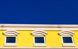Τρία τετραγωνικά παράθυρα σε ένα κίτρινο κτήριο με το φωτεινό μπλε ουρανό ι στοκ εικόνες με δικαίωμα ελεύθερης χρήσης
