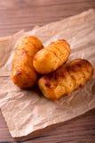 Τρία τριζάτα croquettes πατατών στο κομμάτι του καφετιού χαρτί Στοκ φωτογραφίες με δικαίωμα ελεύθερης χρήσης