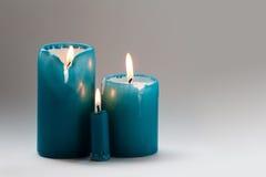 Τρία τυρκουάζ κεριά με ένα καίγοντας φυτίλι Διαφορετικά κεριά μεγέθους, φλόγα κινήσεων Έννοια οικογενειακής ημέρας κλίση Στοκ Εικόνες