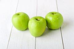 Τρία υγρά πράσινα μήλα στο άσπρο ξύλινο υπόβαθρο κλείστε επάνω Στοκ φωτογραφία με δικαίωμα ελεύθερης χρήσης