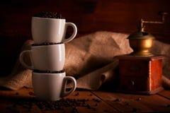 Τρία φλυτζάνια συνόλου των φασολιών καφέ στον ξύλινο πίνακα στοκ εικόνες