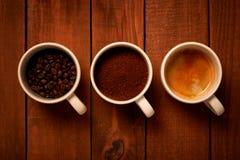 Τρία φλυτζάνια του espresso, πρόσφατα επίγειος καφές και φασόλια καφέ σε έναν ξύλινο πίνακα στοκ εικόνες