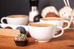 Τρία φλυτζάνια latte και μικρά κέικ στον ξύλινο πίνακα στον καφέ Επικοινωνία πέρα από ένα φλιτζάνι του καφέ, διάλειμμα στοκ φωτογραφίες