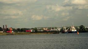 Τρία φορτηγά στο φάρο, γέφυρα και δύο μικρά σκάφη απόθεμα βίντεο