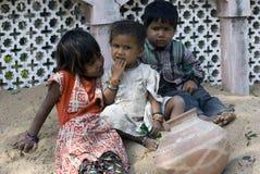 Τρία φτωχά παιδιά τρωγλών που παίζουν στην άμμο Στοκ Εικόνες
