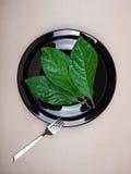 Τρία φύλλα σε ένα μαύρο πιάτο Στοκ φωτογραφία με δικαίωμα ελεύθερης χρήσης
