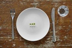 Τρία χάπια στο συμπλήρωμα διατροφής πιάτων Στοκ Εικόνα