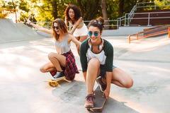 Τρία χαμογελώντας νέα κορίτσια με skateboards στοκ φωτογραφίες