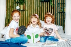 Τρία χαμογελώντας παιδιά μαθαίνουν Προετοιμασία για τους διαγωνισμούς ενάντια ως δολάρια έννοιας δολώματος ανασκόπησης γκρίζα κρε στοκ φωτογραφία με δικαίωμα ελεύθερης χρήσης