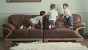 Τρία χαριτωμένα άλματα αδελφών σε έναν καναπέ σε σε αργή κίνηση απόθεμα βίντεο