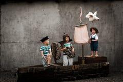 Τρία χαριτωμένα αγόρια στο σκάφος πειρατών ως ναυτικούς στοκ φωτογραφίες με δικαίωμα ελεύθερης χρήσης
