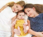 Τρία χαριτωμένα κορίτσια στο κρεβάτι Στοκ Φωτογραφία