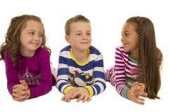 Τρία χαριτωμένα παιδιά που φορούν το χαμόγελο χειμερινών πυτζαμών ευτυχές στοκ φωτογραφία με δικαίωμα ελεύθερης χρήσης