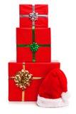 Τρία χριστουγεννιάτικα δώρα και καπέλο Άγιου Βασίλη. στοκ εικόνες