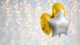 Τρία χρυσά και ασημένια μπαλόνια ηλίου στο λευκό στοκ εικόνες