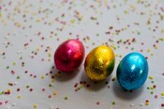 Τρία χρωματισμένα αυγά Πάσχας σοκολάτας στο άσπρο υπόβαθρο και το ζωηρόχρωμο κομφετί στοκ εικόνες