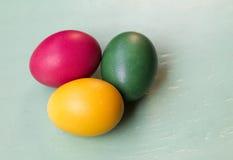 Τρία χρωματισμένα αυγά Πάσχας στο παλαιό ξύλο Στοκ Εικόνα