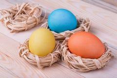 Τρία χρωματισμένα αυγά στις μικρές φωλιές Στοκ Εικόνες