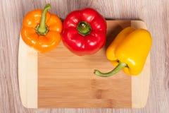 Τρία χρώματα τα πιπέρια στο ξύλινο τέμνον υπόβαθρο Κίτρινα, πορτοκαλιά και κόκκινα πιπέρια Δημοφιλές πιπέρι στην κουζίνα Στοκ Φωτογραφία