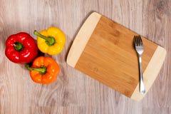 Τρία χρώματα τα πιπέρια στο ξύλινο τέμνον υπόβαθρο με το δίκρανο Κίτρινα, πορτοκαλιά και κόκκινα πιπέρια Στοκ εικόνες με δικαίωμα ελεύθερης χρήσης