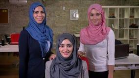 Τρία όμορφα αραβικά θηλυκά στο ζωηρόχρωμα hijab και το πέπλο που εξετάζουν τη κάμερα και που φαίνονται straings με το χαμόγελο, π απόθεμα βίντεο