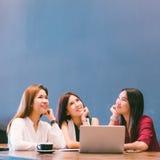 Τρία όμορφα ασιατικά κορίτσια που φαίνονται ανοδικά στο διάστημα αντιγράφων εργαζόμενα στον καφέ Στοκ Φωτογραφία